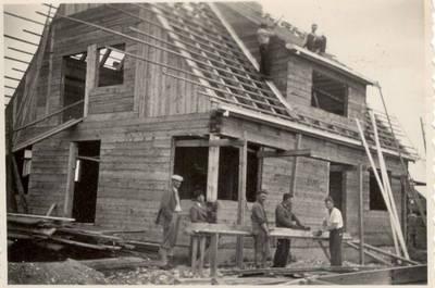 Nežinomas autorius. Nuotrauka. Balys Sruoga su namą statančiais darbininkais. 1938