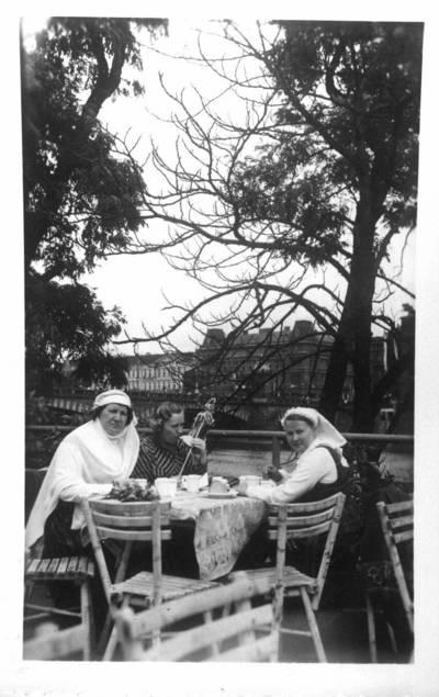 Fotografija. Malvina Valeikienė apsirengusi tautiniais drabužiais sėdi lauko kavinėje su dviemis moterimis Prahoje. 1938