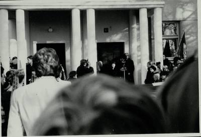 Stasio Adomavičiaus fotografija. Sąjūdis Plungėje 1988-1989. [Sąjūdžio mitingas prie Plungės centrinės bibliotekos pastato, 1988 spalio 30 d. Kalba moteris (neidentifikuotas asmuo), už jos nugaros stovi Alvidas Bakanauskas / Stasys Adomavičius]. - 1988