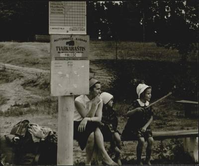 """Šiaulių precizinių staklių gamyklos turistinių žygių dienoraštis. Ikonografija. Šiaulių precizinių staklių gamyklos darbuotojas, turizmo sekcijos narys Jonas Keldušis su šeima keliauja po Rytų Lietuvą. Keliautojai laukia autobusų stotelėje """"Palūšė"""". 1964 m. / medžiaga paruošė D. Balčiūnas. - 1964"""