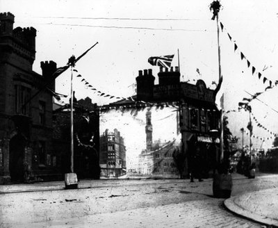 The Sun Inn decorated for the coronation of Edward VII. Either a mural has been painted or a drape has been put on the side of the Inn. On the left can be seen the barracks of the 47th lancashire Rifl
