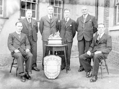 gaskell Deacons First Aid Team with trophies outside the ICI Recreation Club, Liverpool Road. Seated on the left is Mr S Bradshaw and standing third from left is Mr Jack Parker.