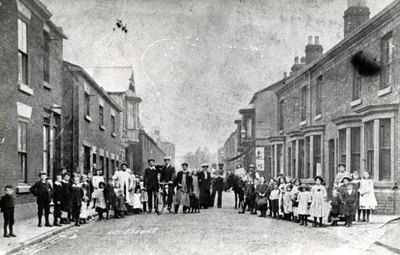 Looking up Farnworth Street with a large group of people standing across the street. The tall building on the left with the bay window was Kirkhams bakery. The rear of the bakery was formerly a Jute F