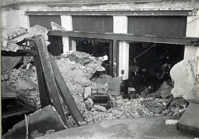 Bomb damage to Widnes Bus Depot in Moor Lane during WWII. The photograph was taken from the remaining portion of the workshop roof showing twisted iron girders and broken concrete. Also shows damage t