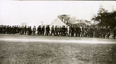 New recruits in civilian dress lined up in front of tents in Heaton Park