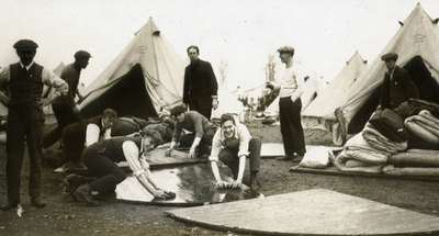 New recruits in civilian dress working on the flooring of the tent