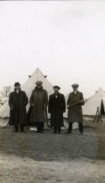 Four new recruits in civilian dress outside tents