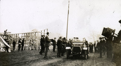 Building hutments at Heaton Park. Shows a car and a man with a camera.