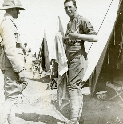 Two unknown men outside tents