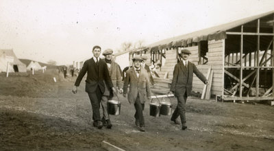 Men from the Pals Battalions carrying carrying hot meals in metal dixies near semi-constructed hutments