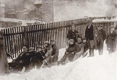 Fabriški delavci na sankah za predilniško ograjo
