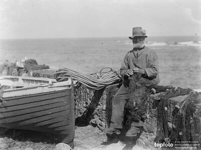 A elderly fisherman sits on