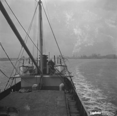 A merchant ship sailing away