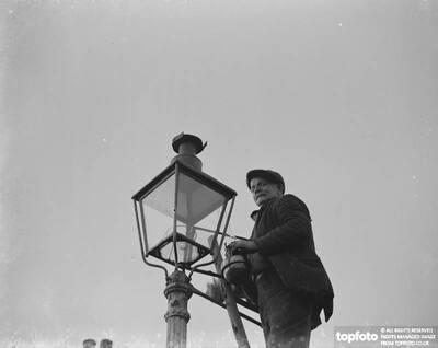 An elderly man lighting an